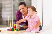 Küçük kız yatakta annesiyle birlikte eğitici oyuncak oynama — Stok fotoğraf