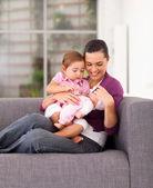 Madre felice riproduzione giocattolo con la figlia sul divano di casa — Foto Stock