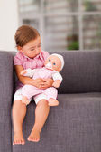 Cute little girl playing with doll at home — Stock Photo