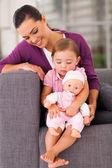 Filha abraçando uma boneca em casa com a mãe — Foto Stock