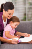 Mother teaching little daughter drawing at home — Stock Photo