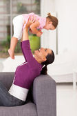 Playful mother playing with little daughter at home — Stock Photo