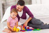 Loving mother watching daughter playing with toy — Stock Photo