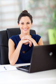 Lovely young white collar worker sitting in office — Stock Photo