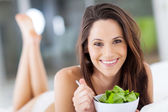 :happy young woman eating green salad on bed — Stockfoto