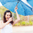Playful young womholding umbrellin rain — Foto Stock #18838021