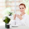 Attractive young woman having coffee in cafe — Stock Photo #18838439