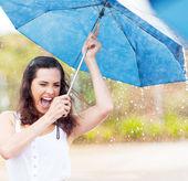 Giocosa giovane donna tenendo l'ombrello sotto la pioggia — Foto Stock