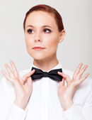 Elegant young woman holding her bow tie and looking away — Stock Photo