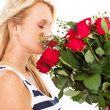 Pretty young woman smelling bunch of roses — Stock Photo #19081655