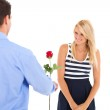 Young man giving rose to a beautiful young woman — Stock Photo