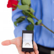 Closeup of young man with engagement ring and rose — Photo