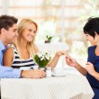 Stock Photo: Happy young woman with fiance showing her engagement ring to her mother