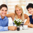 Happy young man with wife and mother-in-law in cafe - Stok fotoğraf