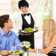Happy waitress serving customers in restaurant - Foto Stock