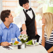 Happy waitress serving customers in cafe — Stock Photo