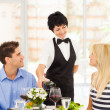 Friendly mature waitress serving wine to diners in restaurant — Stock Photo
