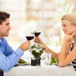 Young couple drinking wine in modern restaurant — Stock Photo