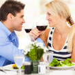 Loving young couple drinking wine in restaurant — Stock Photo