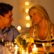 Foto Stock: Young couple enjoying candlelight dinner in a restaurant