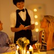 Young couple place dinner order to waitress in a restaurant — Stock Photo