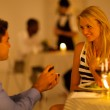 Young man proposing to his girlfriend in a restaurant while having candlelight dinner — Stock Photo #19082531