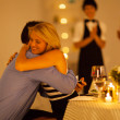 Young woman hugging her boyfriend after he proposed in a restaurant — Stock Photo #19082577