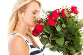 Pretty young woman smelling bunch of roses — Stock Photo