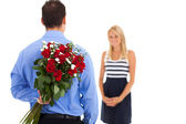 Young man hiding bunch of roses behind his back to surprise his girlfriend on valentine's day — Stockfoto