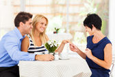 Happy young woman with fiance showing her engagement ring to her mother — Stock Photo