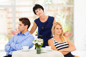 Middle aged mother feeling helpless when caught in between young couple's fight — Stock Photo