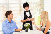Friendly middle aged waitress taking order from customer in restaurant — Stock Photo