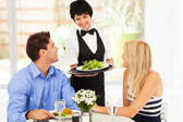 Gelukkig serveerster bedienen klanten in restaurant — Stockfoto