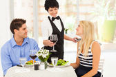 Waitress serving wine to diners in modern restaurant — Stock Photo