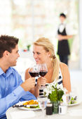 Happy young couple eating out in restaurant — Stock Photo