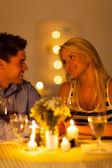 Genç bir çift mum ışığında akşam yemeği restoranda tadını çıkarıyor — Stok fotoğraf