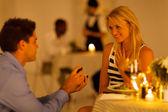 Delikanlı mum ışığında yemek yerken bir restoranda kız arkadaşı için teklif — Stok fotoğraf