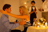 Junge frau, die ihren freund zu umarmen, nachdem er im restaurant vorgeschlagen — Stockfoto