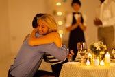 Young woman hugging her boyfriend after he proposed in a restaurant — Stok fotoğraf