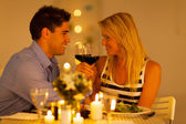 Loving young couple enjoying a glass of wine in restaurant — Stock Photo