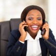 Funny african american businesswoman talking on landline and mobile phone at same time — Stock Photo #19129249