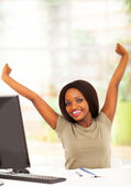 Young african university student stretching before computer — Stock Photo