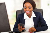 Happy african american busniesswoman reading sms in office — Stock Photo