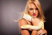 Atrakcyjny blond kobieta pythona na jej ramieniu — Zdjęcie stockowe