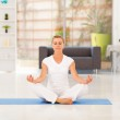 Middle aged woman doing yoga meditation at home — Stock Photo
