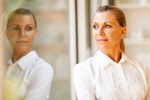 Elegant middle aged businesswoman standing by office window — Stock Photo