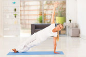 Middle aged woman doing fitness exercise at home — Stock Photo