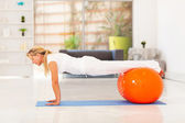 Middle aged woman doing push ups with exercise ball — Stock Photo
