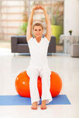 Healthy middle aged woman sitting on exercise ball — Stock Photo