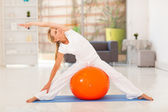 Fit middle aged woman workout with exercise ball — Stock Photo